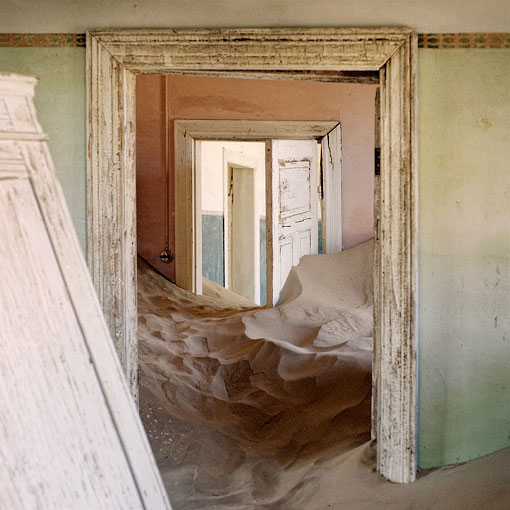 The single men's quarters at Kolmanskop half submerged in sand.