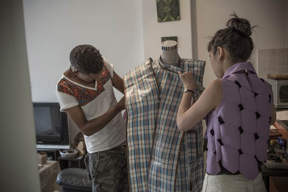 """Working on the collaborative garment with Dennis Chuene made from the ubiquitous """"China Bag"""", Cape Town. Photo by Chris Saunders."""