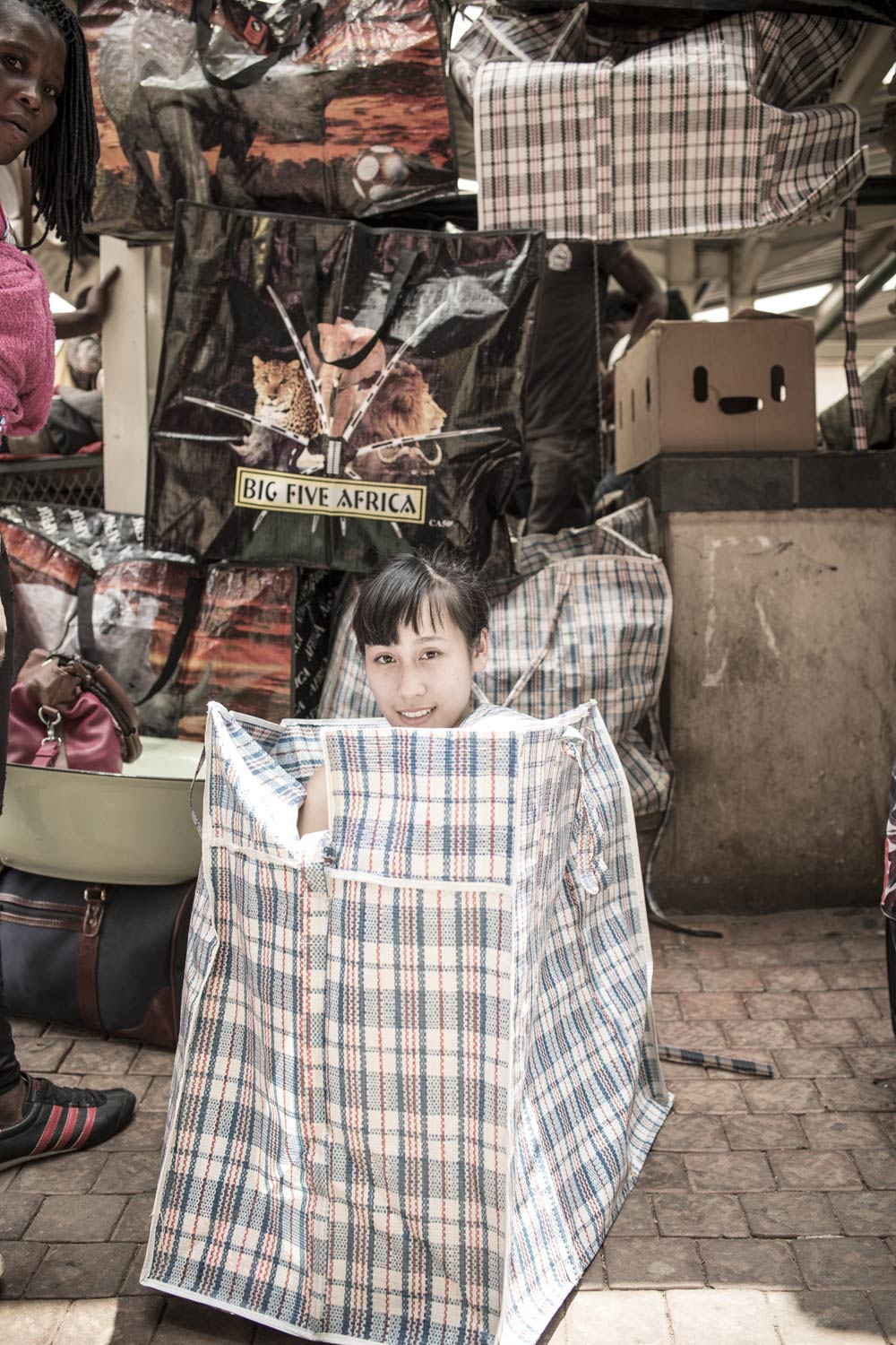 At a local market fashion designer Jenny Lai discovers she fits completely into a China bag. Cape Town, February 2014. Photo | Chris Saunders.