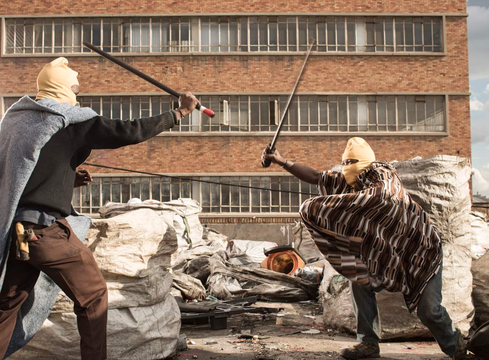 Recyclers behind Chris Saunders' studio stick fighting, a traditional Basotho past time.   Photo by Chris Saunders.