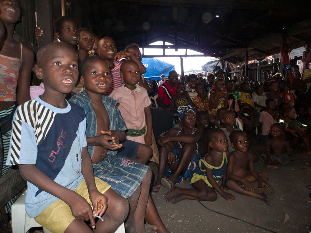Children living in Makoko and, further back, invited guests watching Joel Benson's short documentary on The Silent Majority Project.